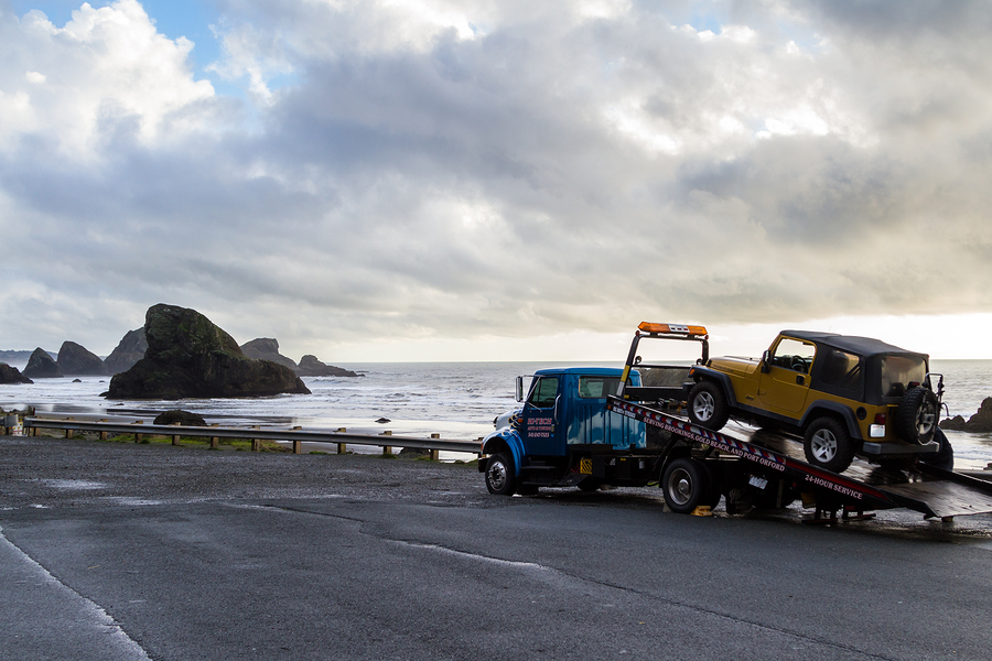 flat bed tow truck loading a broken vehicle with a beautiful coastal landscape in the background