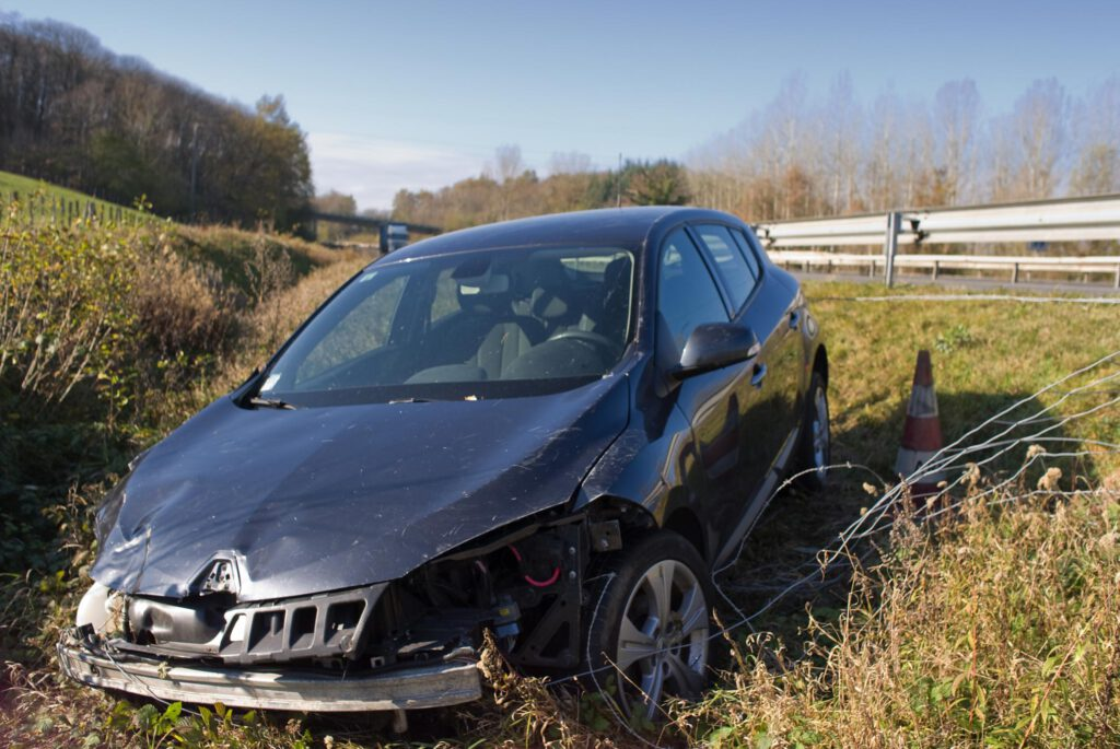 a crashed car on the grassy sideroad
